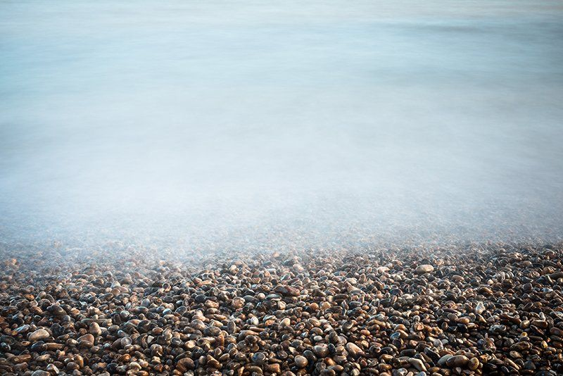 long exposure of tide over pebble beach